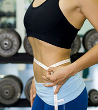 Woman Measuring Waist in a Gym