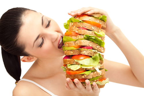 Woman is eating a huge sandwich