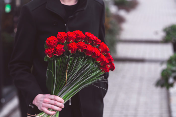 kaboompics-com_young-man-holding-one-big-beautiful-bouquet-of-many-red-rose-flowers